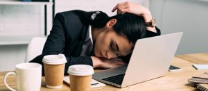 Woman fallen asleep on her desk with laptop and three coffee cups