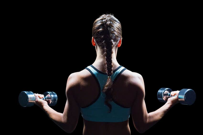Rear view of braided hair woman lifting dumbbells against black background